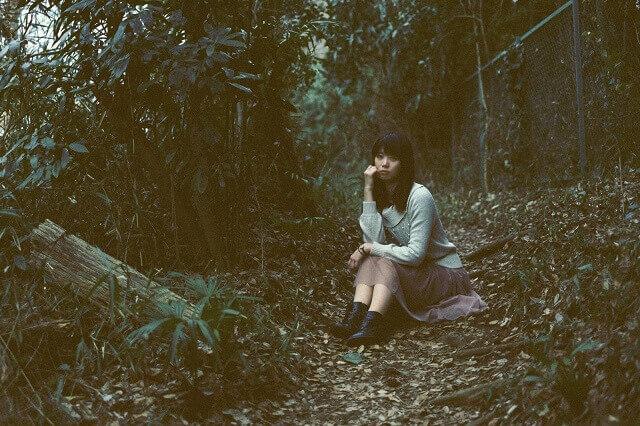 森の中に座る女性