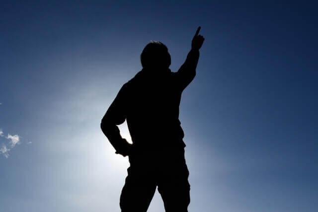天高く指さす男性