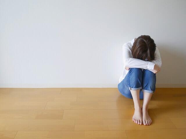 膝を抱えて落ち込む女性