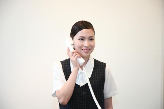 電話を持った受付の女性